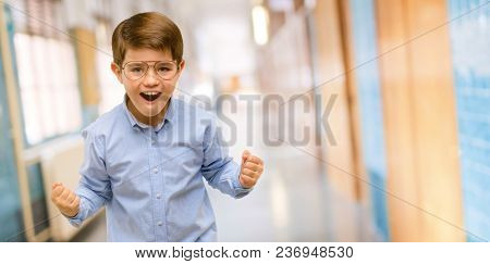 Handsome toddler child with green eyes happy and excited celebrating victory expressing big success, power, energy and positive emotions. Celebrates new job joyful at school corridor