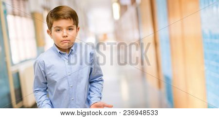Handsome toddler child with green eyes doubt expression, confuse and wonder concept, uncertain future at school corridor