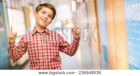 Handsome toddler child with green eyes happy and surprised cheering pointing up at school corridor