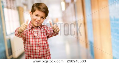 Handsome toddler child with green eyes stand happy and positive with thumbs up approving with a big smile expressing okay gesture at school corridor