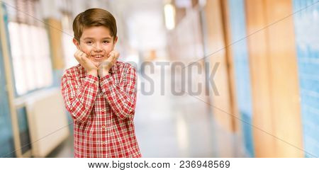 Handsome toddler child with green eyes happy and surprised cheering expressing wow gesture at school corridor