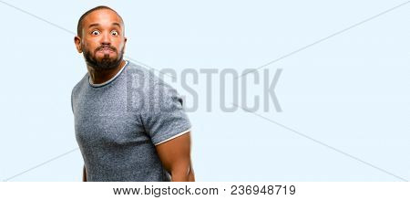 African american man with beard puffing out cheeks, having fun making funny face isolated over blue background