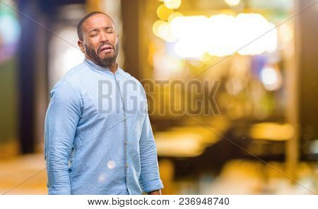 African american man with beard crying depressed full of sadness expressing sad emotion at night