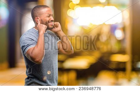 African american man with beard covering ears ignoring annoying loud noise, plugs ears to avoid hearing sound. Noisy music is a problem. at night