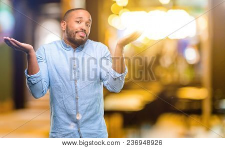 African american man with beard doubt expression, confuse and wonder concept, uncertain future at night
