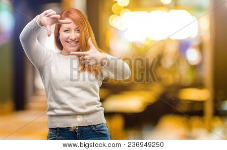 Beautiful young redhead woman confident and happy showing hands to camera, composing and framing gesture at night