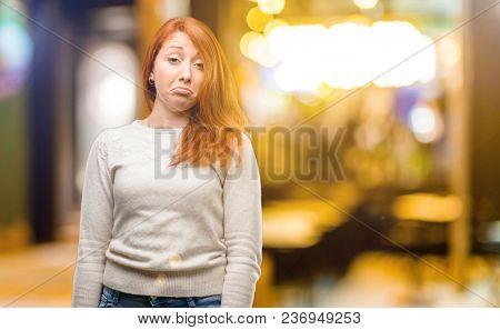 Beautiful young redhead woman having skeptical and dissatisfied look expressing Distrust, skepticism and doubt at night