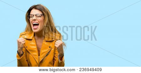 Beautiful young woman happy and excited celebrating victory expressing big success, power, energy and positive emotions. Celebrates new job joyful