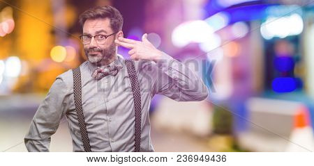 Middle age man, with beard and bow tie unhappy making suicide gesture, tired of everything. Shoots with hand imitating gun, upset at night club