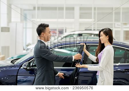 Lovely Smiling Asian Woman Buying New Car