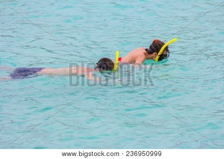 Beach Vacation Couple Wearing A Snorkel Scuba Mask Making A Goofy Face While Swimming In Ocean Water