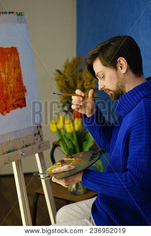Artist In Blue Sweater Pondered. He Holds Palette, Bristle Brush. Man Is Sitting In Front Of Easel.