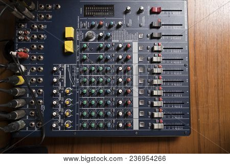 Top View Of Professional Sound Mixer Controller On Wooden Table.