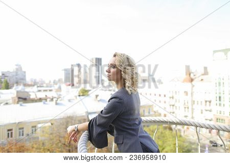 Pretty Female Person Standing On Balcony With Cityscape Background. Concept Of Vogue And Urban Life