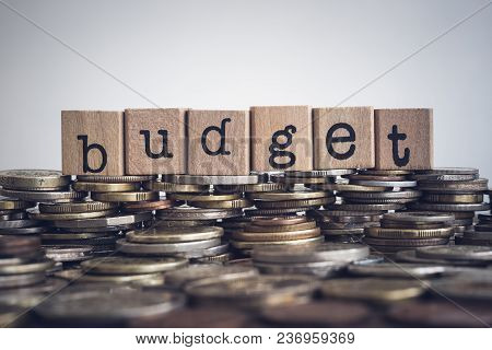 The Word Budget, Text On Wooden Cubes On Currency Money, Top Of World Coins Stack. Concepts Of Wealt