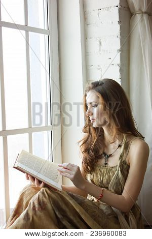 Beautiful Young Woman Sitting At A Window And Reading Book