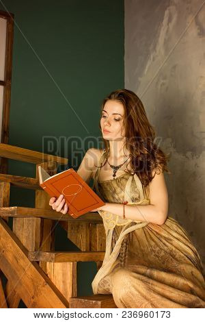Beautiful Young Woman Reading Book Reads A Book Sitting On A Wooden Staircase