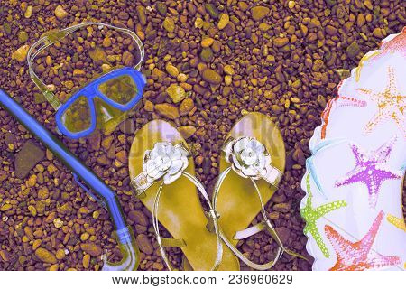 Surrealism Beach Accessories On The Sea Pebble. Lifeline Underwater Mask Tube Sandals. Flat Lay Top