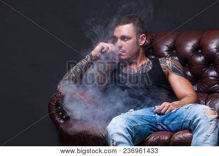 View From The Side Of A Young Man Smoking An E-cigarette As He Drives His Car On An Urban Street. At