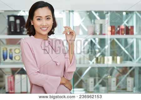 Attractive Young Shop Assistant Wearing Pink Blouse Looking At Camera With Charming Smile While Stan