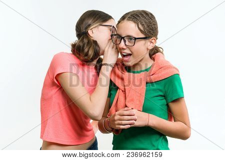 Portrait Of Two 12-13 Year Old Girls. Beautiful Teenage Girlfriends Communicate, Secrete And Smiling