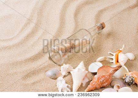 Message In Bottle On The Beach. Summer Background With Hot Sand