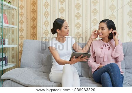 Highly Professional Vietnamese Cosmetologist Sitting On Cozy Sofa, Examining Facial Skin Of Pretty C