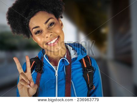 Millennial backpacker making peace sign against blurry train station