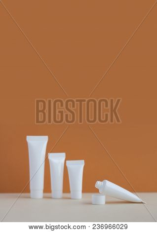 White Cosmetic Tubes On Brown And Beige Background. Blank Opened Plastic Container, Simple Packaging