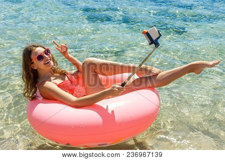 Crazy Swimming With Inflatable Donut Makes Selfie On The Beach In Summer Sunny Day.