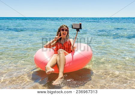 Happy Smiling Girl Makes Selfie Floating On Inflatable Donut In Sea. Vacation Time.