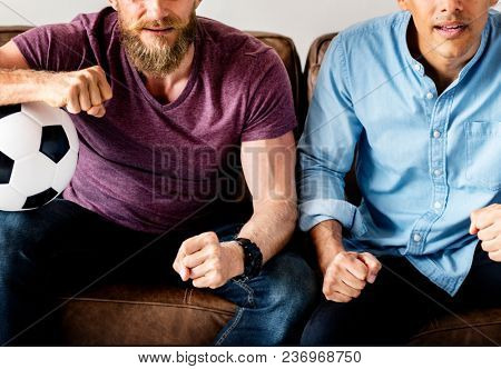 Man sitting together on a couch watching sport