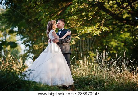 Newly Married Couple Enjoying Each Other's Company In The Forest At Sunset On Their Wedding Day.