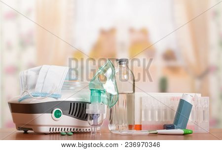 Compressor Nebulizer And Small Pocket Inhaler, Medication, Pills, Thermometer On Background Of Table