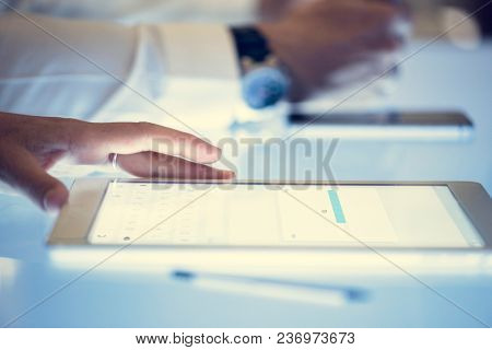 Hand on a digital tablet with downloading on a screen