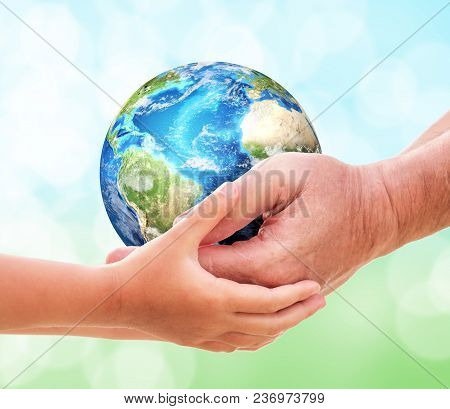 The Man Gives Planet Earth To Baby Over Nature Background. Ecology Concept, Earth Day, World Environ