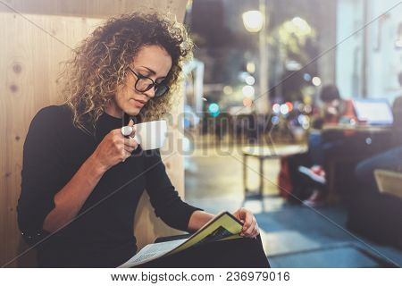 Charming Fashionable Woman With Eyes Glasses In A Black Sweater Sits At A Table In A Cafe At Night A