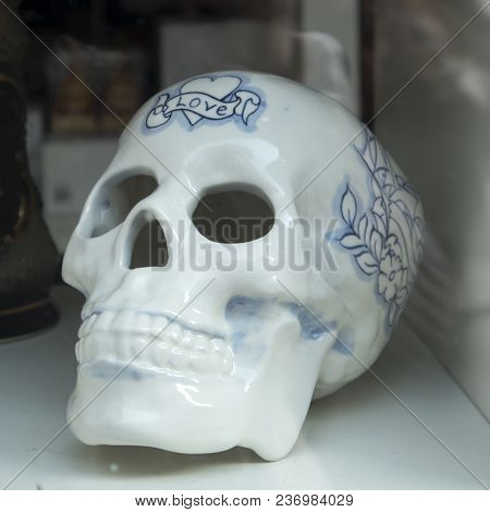 Amsterdam, Holland - 14 April 2018 Porcelain White Skull With A Blue Inscription Love In Traditional