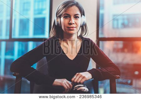 Beautiful Blonde Girl Wearing Eye Glasses And Casual Clothes Listening Digital Music In Headphones O