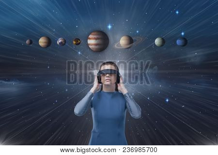 Woman in VR headset looking up to 3D planets against blue sky with flare