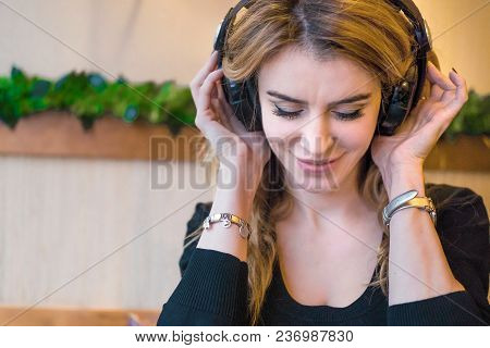 Beautiful Middle Aged Woman In Cafe, Smiling Woman Listening To The Music Via Headphones At A Cafe,