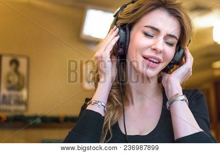 Beautiful Middle Aged Woman In Cafe, Smiling Woman Listening To The Music Via Headphones And Singing