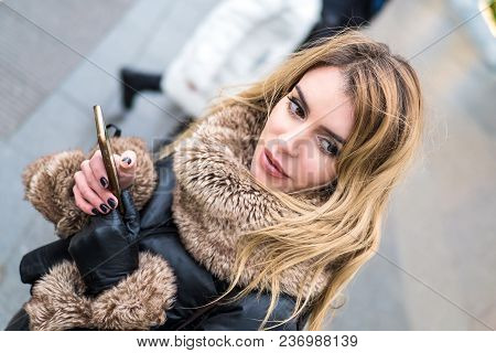 Woman In Unknown City Using Gps Navigation On Phone. Online Booking. Autumn Fashion Style. City Tour