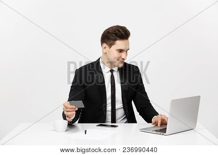 Young Businessman With Notebook And Credit Card Isolated Over White Background.