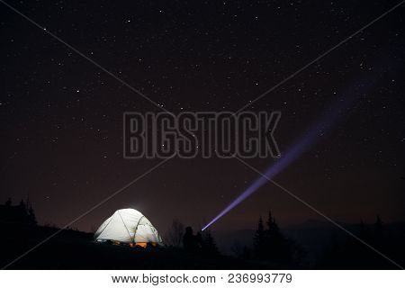 Man Tourist With Flashlight Near His Camp Tent At Night Under A Sky Full Of Stars. Night Mountain Lo