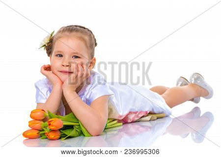 Charming Little Girl In A Beautiful Dress Lies On The Floor With A Bouquet Of Tulips. Concept Of Hap