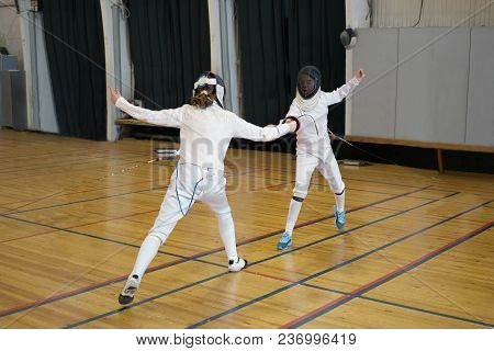 Girls, Participants In Fencing Competitions Are Fighting On Swords, Epees. One Girl Is Pricking Anot