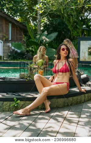 Beautiful Young Woman In Bikini And Sunglasses Resting At Swimming Pool