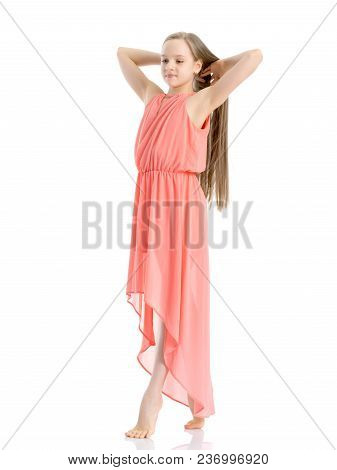 A Charming Little School Girl Corrects Her Long Silky Hair With Her Hands. The Concept Of Style And