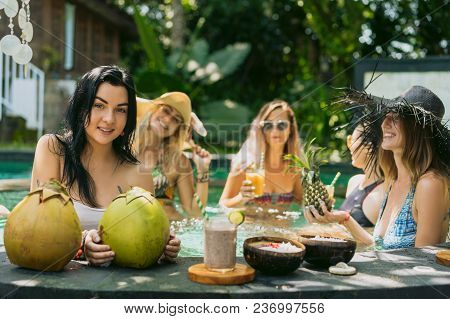 Young Women In Swimwear Drinking Tropical Cocktails And Relaxing In Swimming Pool